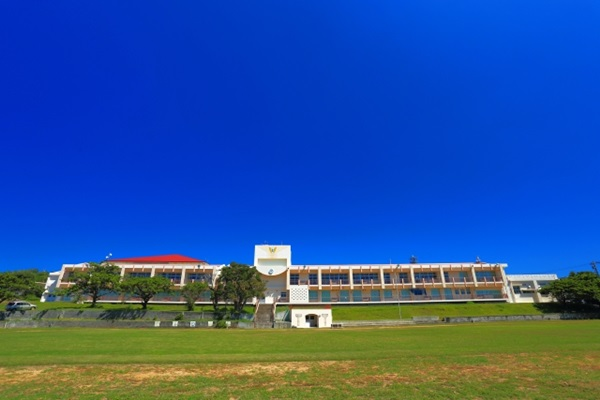雲ひとつない晴天の空と学校校舎、芝生のグラウンド