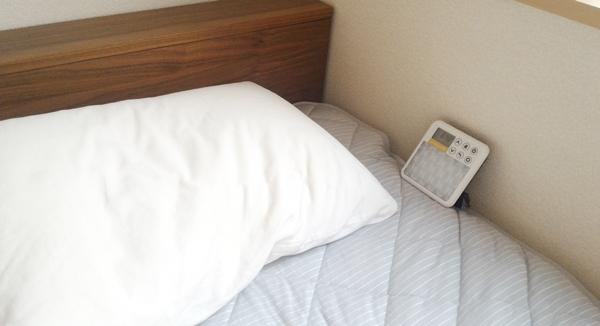 ベッドの枕の横に光目覚ましを置いている様子