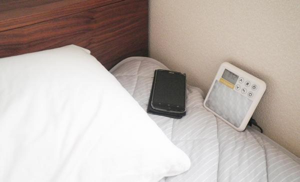 枕横にアラームを設定したスマホと光目覚まし時計inti SQUAREを置いている様子