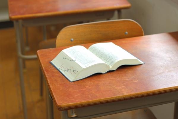 辞書が置かれた学校の教室の木製机