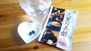 三黒の美酢のパッケージ袋と粒2つとコップ1杯の水