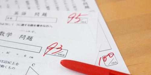 採点済みのテストの答案用紙と赤ペン